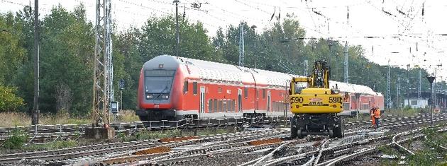 Ein Personenzug und ein Gleisbaufahrzeug im Betrieb