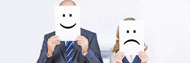 Zwei Personen halten sich jeweils ein Blatt mit unterschiedlichen Emotionen vor das eigene Gesicht