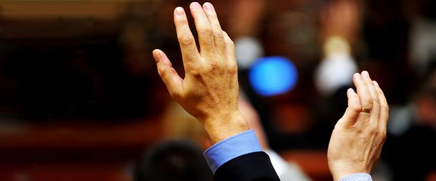 Zwei erhobene Hände zweier verschiedener männlicher Personen als beispielhafte Abstimmung in der Selbstverwaltung