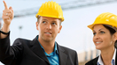 Mann uind Frau mit Schutzhelmen auf einer Baustelle