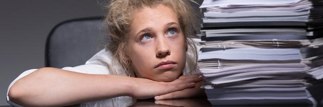Eine junge Frau sitzt verzweifelt vor einem hohen Stapel Akten.