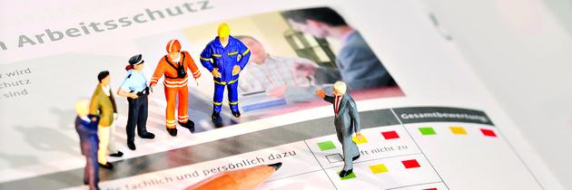 Beispielhafte Versicherte verschiedener Berufsgruppen erhalten eine Einweisung vor dem Hintergrund eines Analysebogens zum Arbeitsschutz
