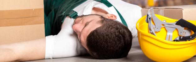 Ein Mann ist bei der Arbeit gestürzt und liegt auf dem Boden.