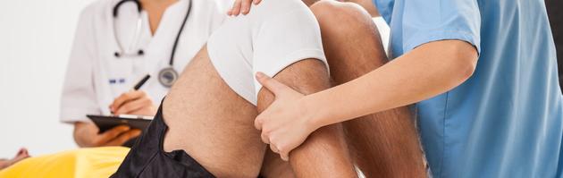 Physiotherapeut überprüft die Funktion des Knies eines Patienten