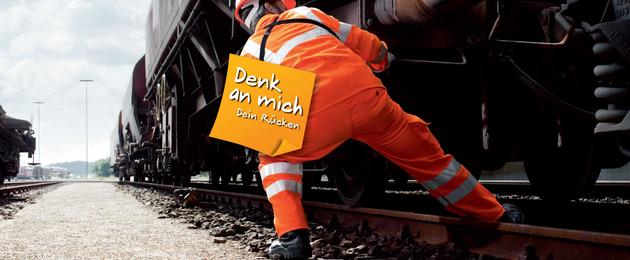 """Ein Bahnmitarbeiter arbeitet an einem Waggon, an seinem Rücken prankt die Aufschrift """"Denk an mich. Dein Rücken"""""""