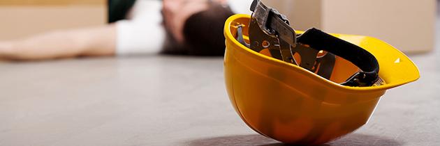 Ein Mann in Arbeitskleidung liegt am Boden. Der Sicherheitshelm ist herunter gefallen und liegt neben ihm am Boden.