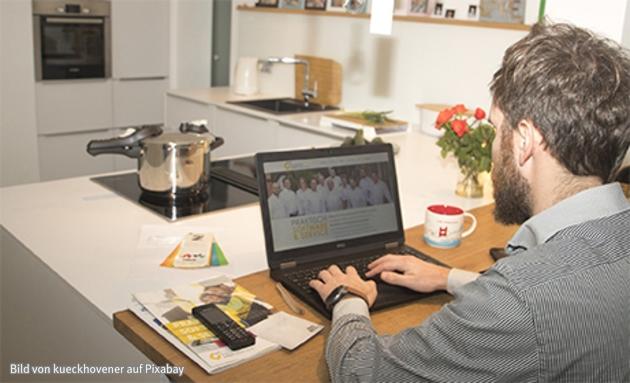 Das Büro nach Hause verlegt. Ein Mann arbeitet in seiner Küche beruflich an einem Notebook.